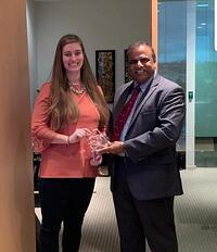 Kasey Tyring receiving an award from Purna Veer