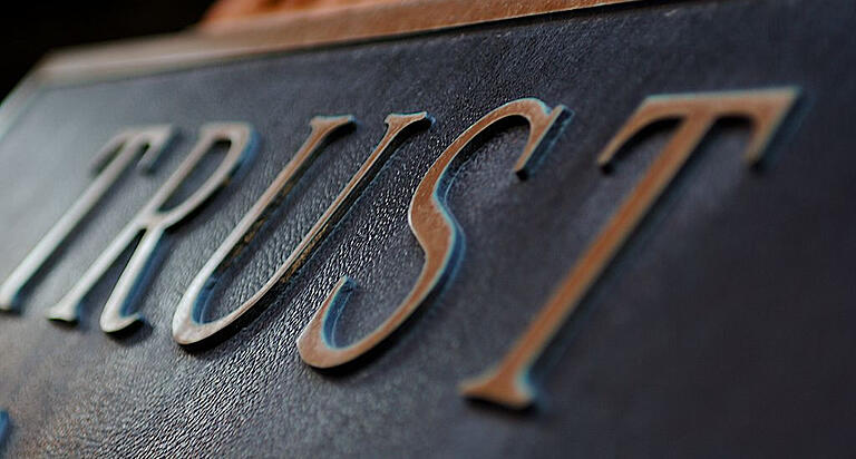 Trust embossed on a sign indicating trust is inherit in blockchain